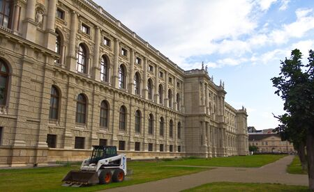View of the Natural History Museum in Vienna, Austria, with a small shovel vehicle beside it.