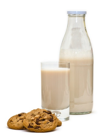 Typical kids breakfast with chocolate chip cookies, a glass of milk and a classic bottle of milk, with limited depth of field. Isolated on white.