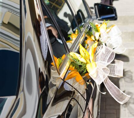 Luxury wedding car decorated with flowers with the reflection of people waiting for the bride.