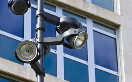 Detail of a modern lamppost with several lamps in front of a corporate building with glass windows. Stock Photo - 11143492