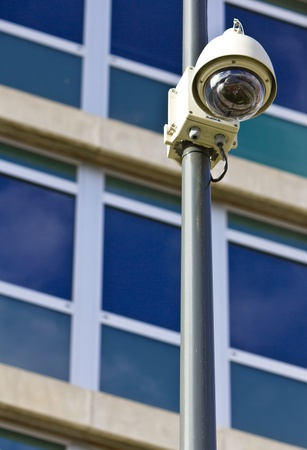 Surveillance camera on a pole, low angle view, with a corporate building behind. Stock Photo - 11143488