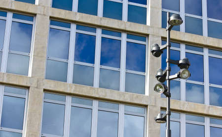 A modern lamppost with several lamps in front of a corporate building with glass windows. Stock Photo - 11511853
