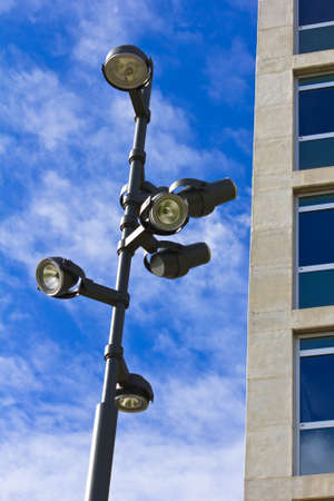 A modern lamppost with several lamps over blue sky in front of a corporate building with glass windows. Stock Photo - 11511851