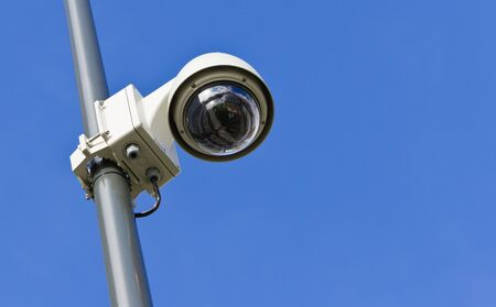 360 degrees surveillance camera on a pole, low angle view, blue sky.