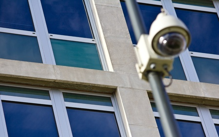 Surveillance camera on a pole out of focus, with a corporate building behind. Stock Photo - 11511852