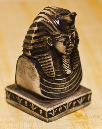 Small statue of egyptian pharaoh Tutankhamun, side view, over a papyrus paper background, selective depth of field. Stock Photo - 11802337