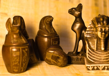 Several egyptian souvenirs over papyrus paper background, selective depth of field. photo