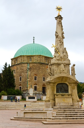 The mosque of Gazi Kaszim and the Trinity Statue in the main square of Pecs, Hungary.