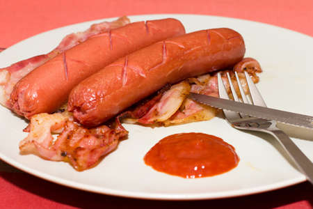 Sausages and bacon with ketchup, concept for junk food.