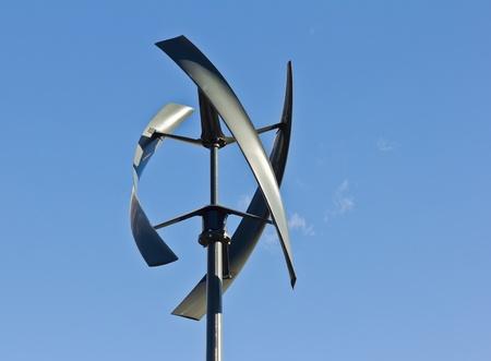 Silent urban styled wind turbine with blue sky. Stock Photo