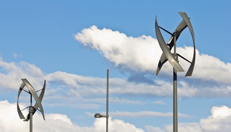 Couple of silent urban styled wind turbines, blue sky. Stock Photo