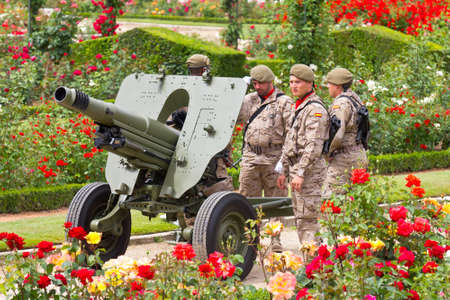 VALLADOLID, SPAIN – JUNE 2, 2012: Group of soldiers with a cannon in a garden in the Armed Forces Day 2012, on June 2, 2012 in Valladolid, Spain.
