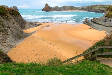 Tiny beach in Cantabria with cliffs and wooden stairs to get inside.
