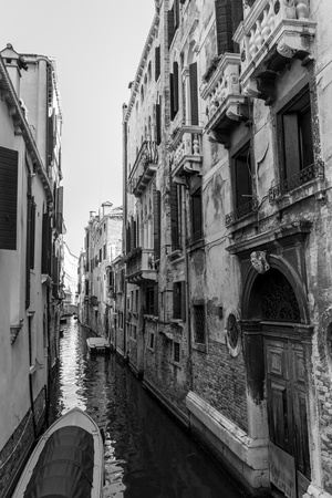 Black and white Venice channel with aged ruined buildings.