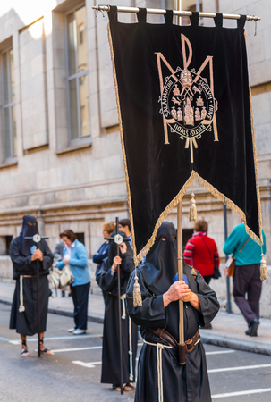 crucis: VALLADOLID, SPAIN � APRIL 17, 2014  Black nazarenos with a flag in the religious processions with a musical band behind during Holy Week on Good Thursday, on April 17, 2014 in Valladolid, Spain