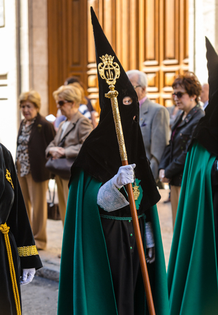 holy thursday: VALLADOLID, SPAIN – APRIL 17, 2014  Black and green nazareno in the religious processions during Holy Week on Good Thursday, on April 17, 2014 in Valladolid, Spain