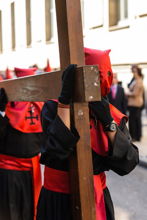 holy thursday: VALLADOLID, SPAIN � APRIL 17, 2014  Red and black nazareno carrying a wooden cross in the religious processions during Holy Week on Good Thursday, on April 17, 2014 in Valladolid, Spain