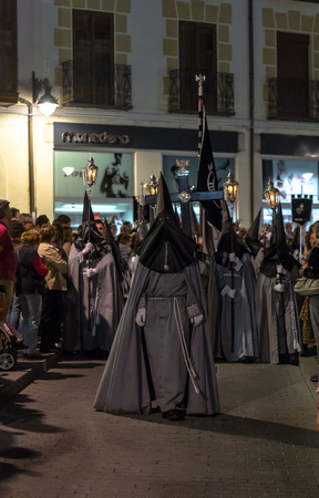 penitence: VALLADOLID, SPAIN - APRIL 18, 2014  Black and grey nazarenos in the religious processions during Holy Week on Good Friday Night, on April 18, 2014 in Valladolid, Spain