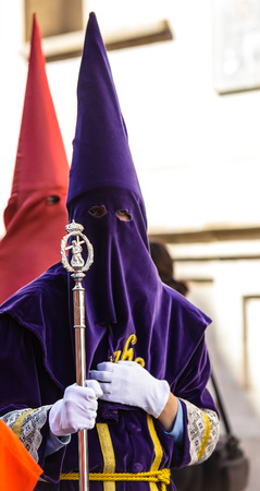 holy thursday: Purple nazareno with a Jesuschrist Cane in the Good Thursday during Holy Week in Valladolid