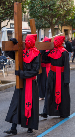 carrying the cross: Red and black Nazarenos carrying a cross in the Good Thursday during Holy Week in Valladolid.