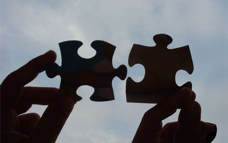 hands trying to fit two puzzle pieces together Stock Photo - 502388