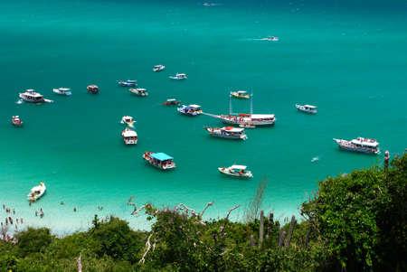Boats over a crystalline turquoise sea in Arraial do Cabo, Rio de janeiro, Brazil photo