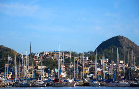 krottenwijk: Slum buurt van de zee, met rijke boten en yachtes voor
