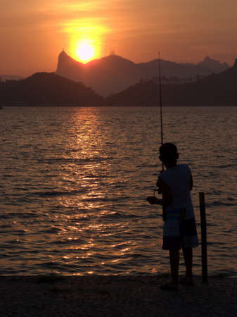 Kid fishing on the sunset in Rio de Janeiro photo
