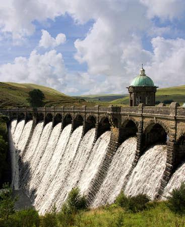 Water overflowing a dam, Craig Goch reservoir, Elan Valley Wales. photo