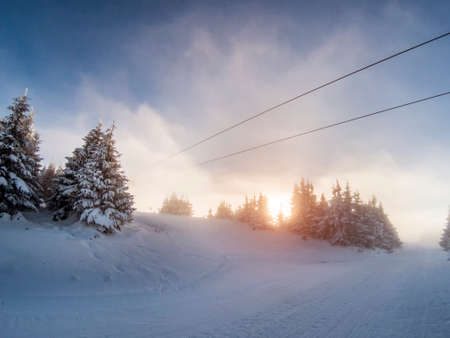 Hazy dieing sun on a ski slope with icy snow covered trees Stock Photo