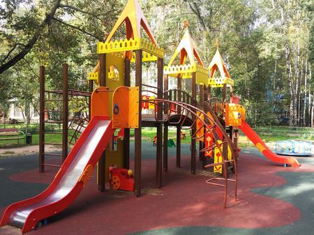 niños en recreo: Colorful playground on yard in the park.