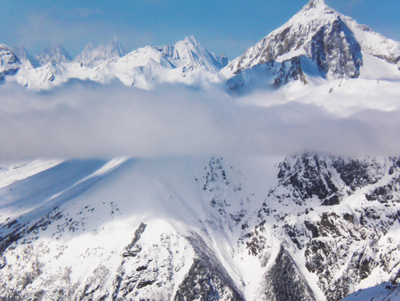 Views of snow capped mountains of Dombay. Winter Sunny day, looming snow clouds. mountain range, avalanche