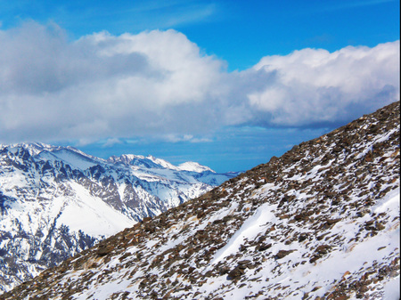 Views of snow capped mountains of Dombay. Winter Sunny day, looming snow clouds, mountain range, avalanche