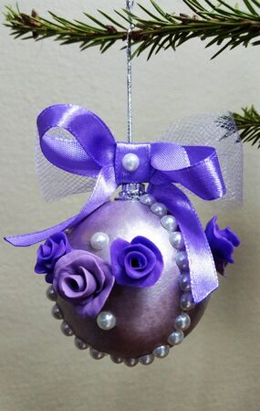 Christmas toy on a fir branch. Homemade purple Christmas toy.