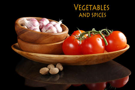 Tomatoes and garlic in wooden plate on black background Stock Photo - 13167183