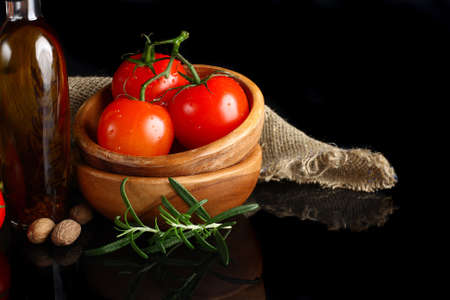 Tomatos and garlic in wooden plate on black background   photo