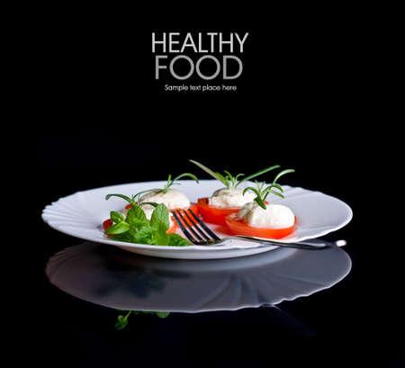 plato de comida: Los tomates y el ajo en plato de madera sobre fondo negro