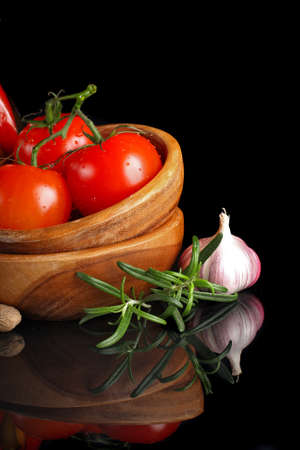 Tomatoes and garlic in wooden plate on black background   photo