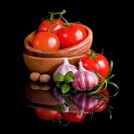 tomate cherry: Los tomates y el ajo en plato de madera sobre fondo negro