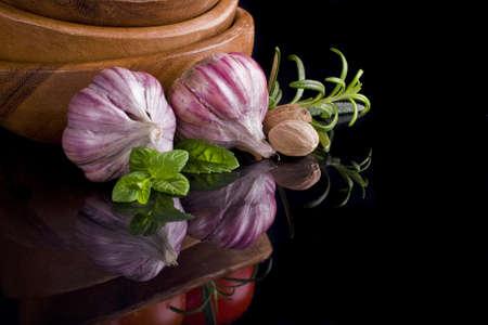garlic in wooden plate on black background   photo