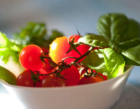 Fresh cherry tomatoes in a stylish white bowl   photo