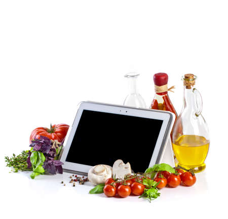 Tablet computer with vegetables on white background
