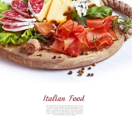 Italian cuisine. Prosciutto, cheese, salami, herbs. Stock Photo