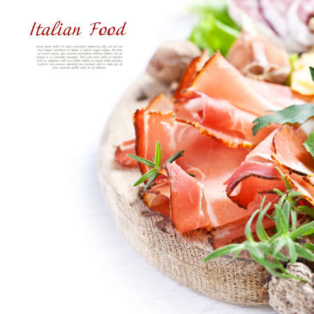 Italian cuisine. Prosciutto, cheese, salami, herbs. Stock Photo