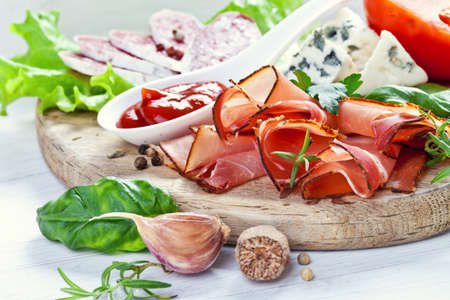 Sliced prosciutto with salami,cheese and basil on a wooden board photo