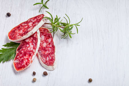 air dried salami: Salami on wooden board with rosemary Stock Photo
