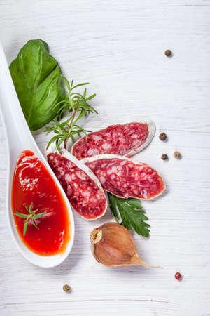 longaniza: Salami on wooden board with rosemary Stock Photo