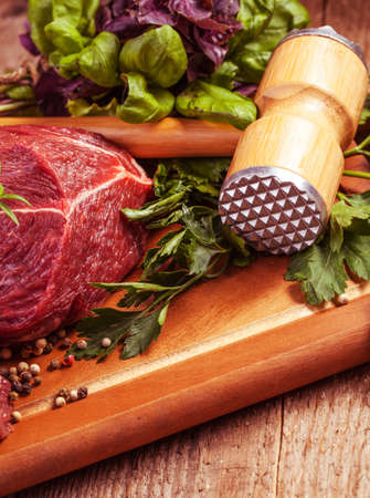 Raw meat on wooden cutting board with herbs photo
