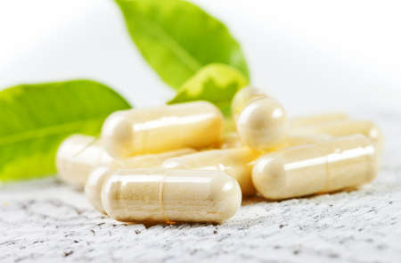 Capsules on white wooden background. Stock Photo