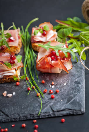 prosciutto: Sliced prosciutto with herbs and pomegranate seeds Stock Photo